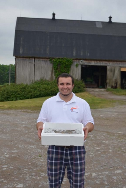 Behind Edible Ottawa's Cover: Brad Cocchio poses with shrimp raised in converted hog barns in Campbellford, Ont.